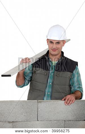 Bricklayer with a board of wood