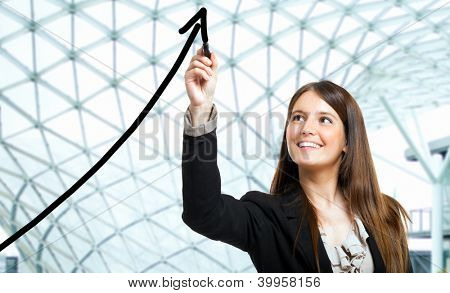 Beautiful woman tracing a rising arrow, representing business growth