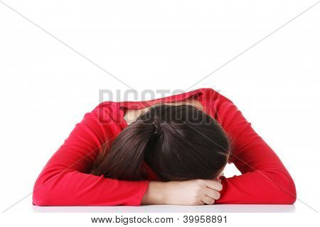 Young woman sleeping on desk, isolated on white