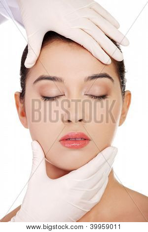 Plastic surgery concept. Doctor hands in gloves touching the beautiful woman face. Isolated on white