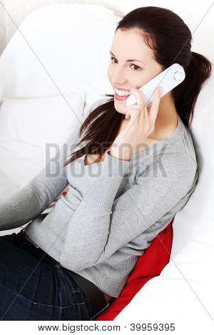 Attractive young woman sitting on a sofa and talking on a phone.