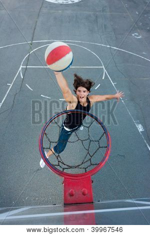 Young basketball player on the street going to the hoop. Great angle from above. Focused on the basket