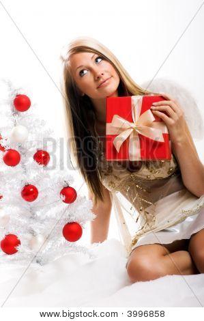 Ángel con un regalo y un árbol de Navidad