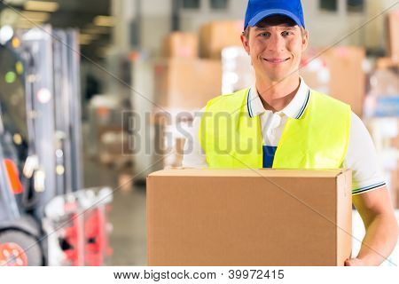 Warehouseman with protective vest holds package, he standing at warehouse of freight forwarding company