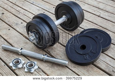 cast iron dumbbell and weight plates on wooden deck - home gym concept