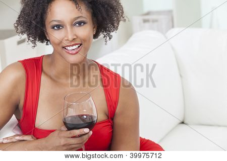 A beautiful mixed race African American girl or young woman wearing a red dress looking happy and drinking red wine