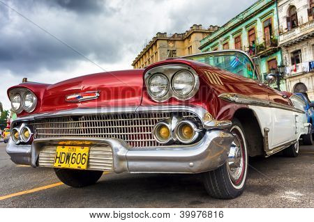 HAVANA-NOVEMBER 28:Old red Chevrolet near the Capitol November 28,2012 in Havana.Thousands of these cars are still in use in Cuba and they have become an iconic view and a worldwide known attraction