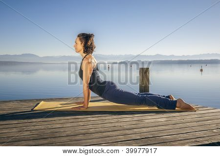 An image of a pretty woman doing yoga at the lake