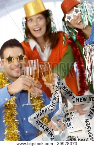 Office workers celebrating new year wearing funny party accessories.