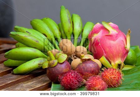 Display of tropical fruit on banana leaf on wooden table in natural light