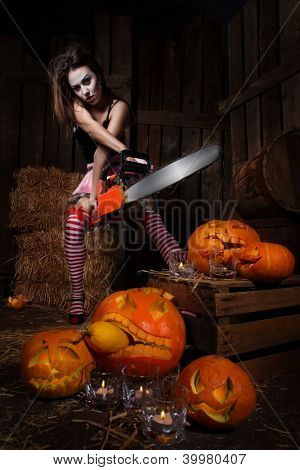 Beautiful sexy woman with halloween pumpkin against wooden background