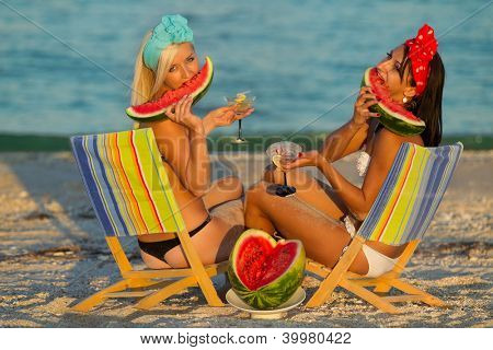 Young stylish ladies at sea with watermelon and a drink relaxing on deck chair