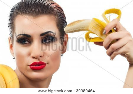 Close-up female pointing peeled banana on her head
