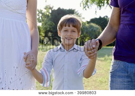 Happy Family With Son And Parents Holding Hands