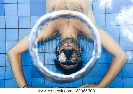 Man making bubble rings underwater in pool