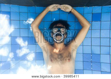 Man making bubble rings underwater in pool