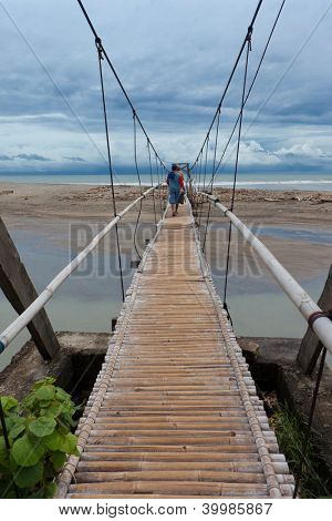 Men walking on suspension bridge over small river leading to the sea in Bali.