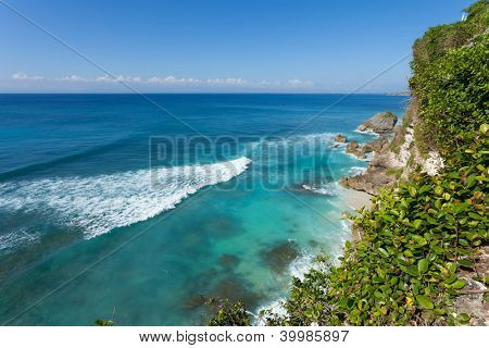 UluWatu coastline with beaautiful rocky cliffs and turquoise wavey sea.