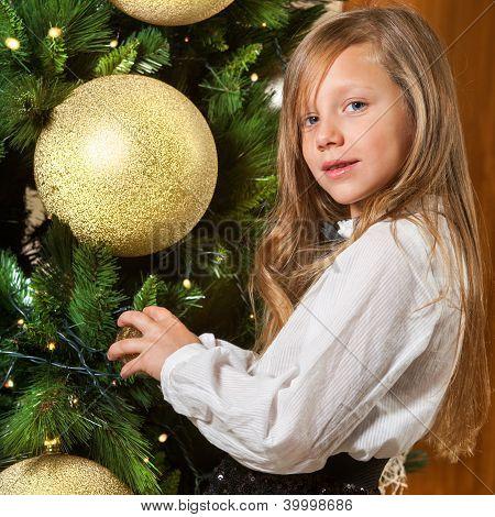 nettes Mädchen schmücken Weihnachtsbaum.