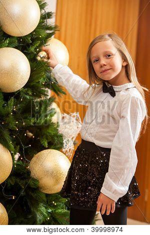 kleine Mädchen schmücken Weihnachtsbaum.