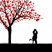 stock photo of beside  - Silhouette of kissing couple beside love tree - JPG