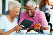 image of hot couple  - Senior Couple Using Tablet Computer At Outdoor Cafe - JPG