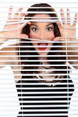 Woman peeking through blinds