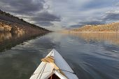 pic of horsetooth reservoir  - expedition decked canoe and wooden paddle on a narrow mountain lake  - JPG