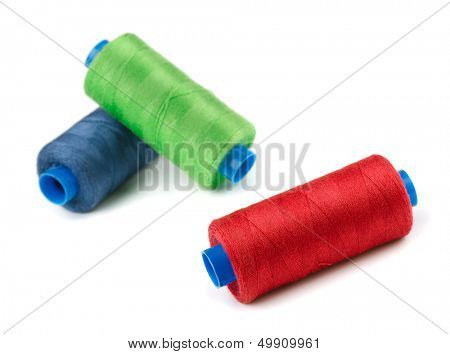 Three spools of color thread isolated on white