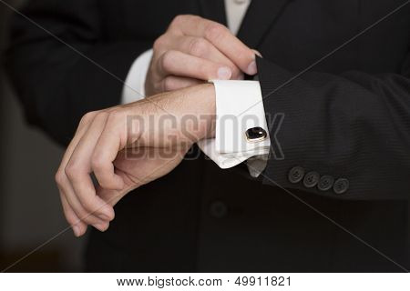Wedding details, cufflinks, elegant male suit and hands