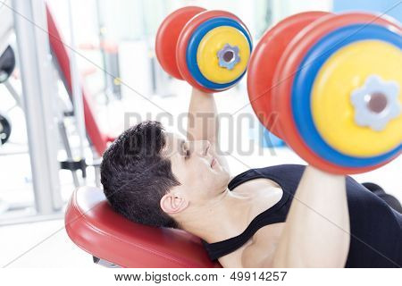 Young handsome man lifting heavy free weights at the gym