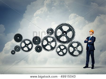 Businessman with cog wheel elements. Construction concept