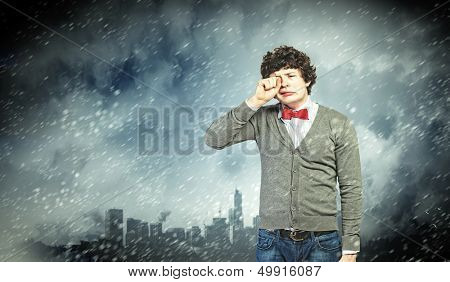 Image of young upset man in red tie crying