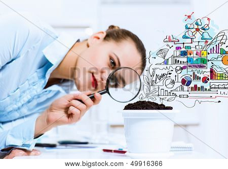 Young businesswoman looking at drawn image of sprout through magnifier