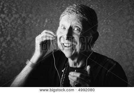 Elderly Hiptser Listening To Handheld Audio Device