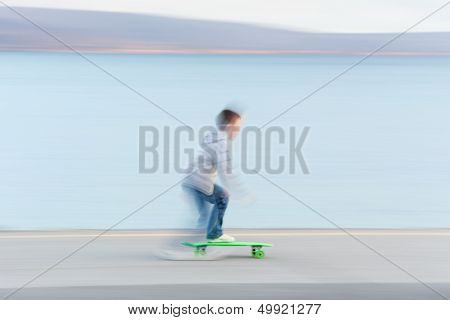 Boy Riding Skateboard. Blurred Motion