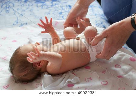 1 week old newborn and pediatrician hands