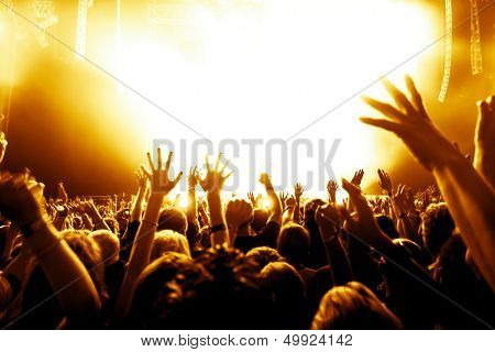 silhouettes of concert crowd in front of bright stage lights poster