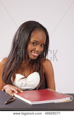 Black woman smiling with red notebook