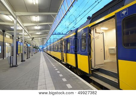 """VENLO, NETHERLANDS - JUNE 22: Commuter train on a train station of Venlo, Netherlands on June 22, 2013. Dutch trains are on the whole punctual with 94% (2012) of train services labeled """"on time"""""""