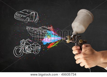 Man with airbrush spray paint with car, boat and motorcycle drawing on dark background