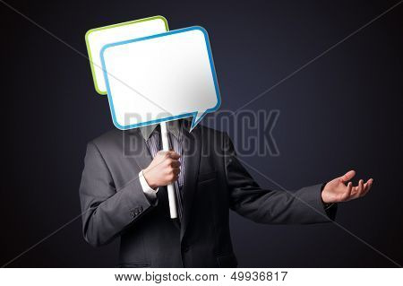 Businessman standing and holding an empty speech bubble in front of his head