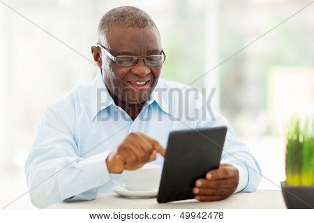 alegre homem afro-americano sênior, usando o tablet PC em casa