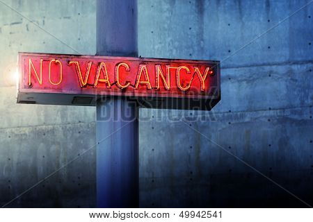 Glowing retro neon 'no vacancy' sign against cool blue wall background