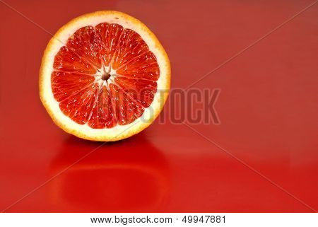 Juicy half of a blood orange on a red background horizontal view