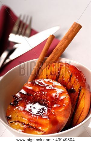 Grilled peaches in a bowl with raspberry sauce and cinnamon sticks