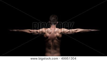 Muscular Man With Arms Streched Out On Black Background