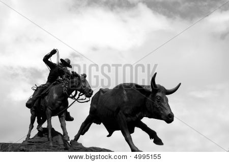 Statue Of A Man Roping A Bull.