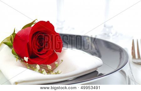 Romantic dinner setting with a rose and champagne glasses
