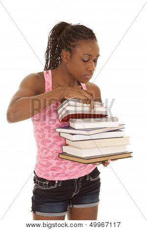 Woman Pink Tank Look Through Stack Of Books